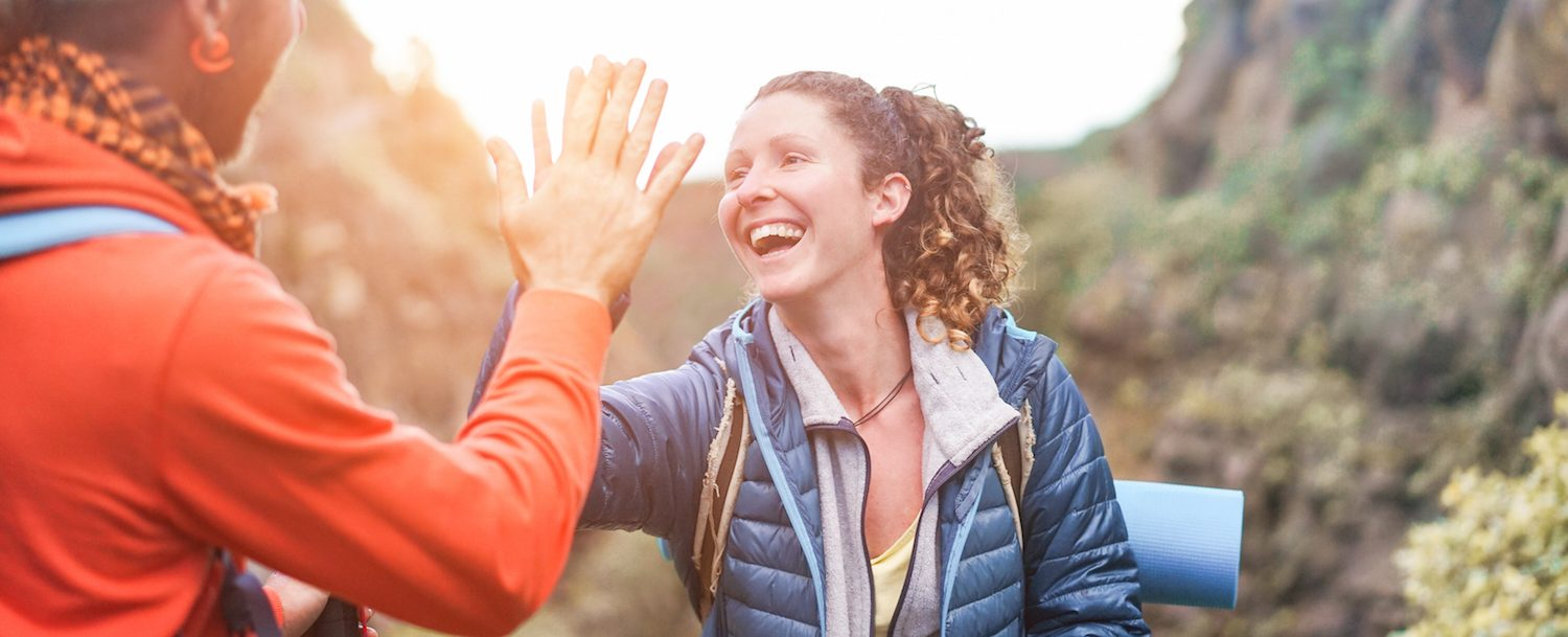Two woman high fiving on a hike.