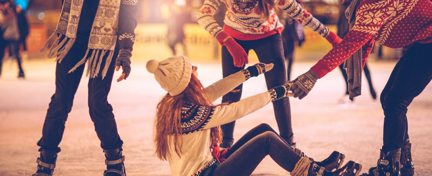 Friends having so much fun while ice skating. Wearing warm clothing. City is decorated with christmas lights.