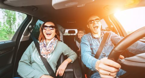 Cheerful young traditional family has a long auto journey and singing aloud the favorite song together. Safety riding car concept wide angle view image.